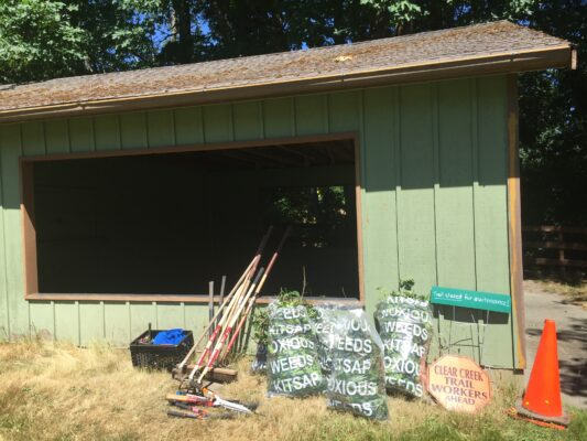 Filled bags of noxious weeds and other tools in front of the Clear Creek Trail's Ridgetop Pavilion