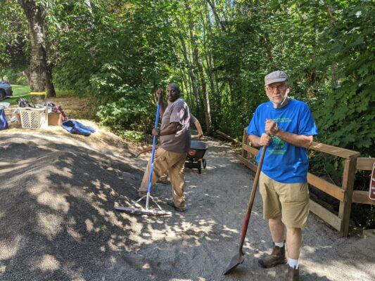 Several volunteers raking gravel at the Clear Creek Trail