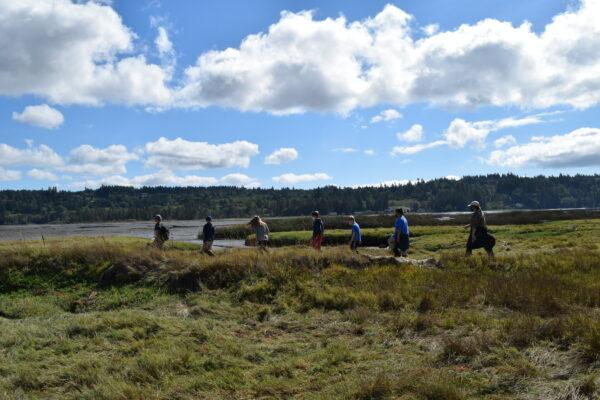 Students walk along the shoreline at Klingel-Bryan Beard Wildlife Refuge, under a bright blue sky with clouds.