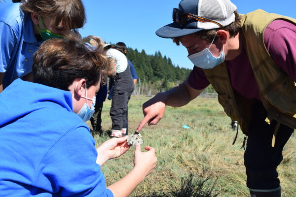 An instructor points to an oyster shell held by a student