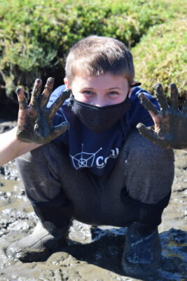 A student shows off his muddy hands